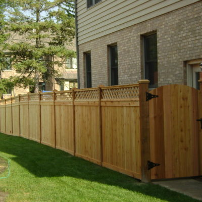 Photo of a custom traditional wood fence with a lattice topper designed and installed by First Fence Company