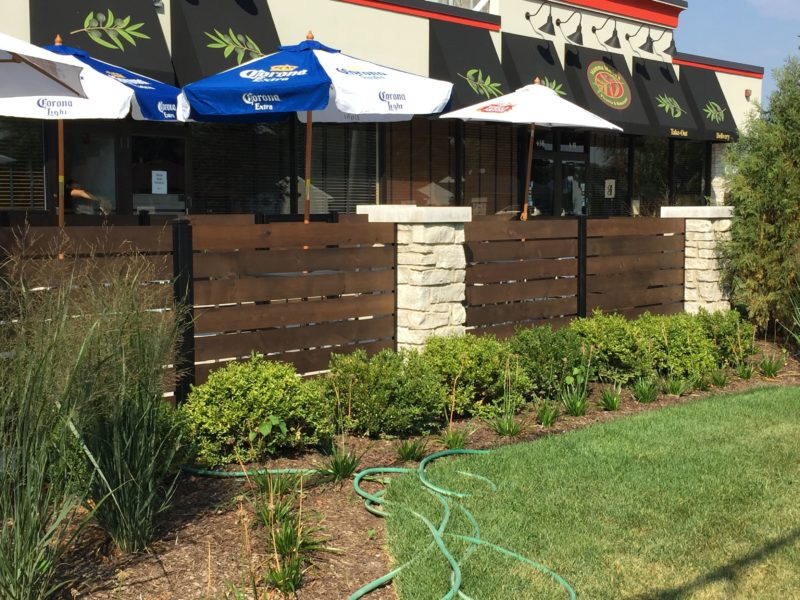 Horizontal Wood Patio fence and masonry pillars. Fence designed, stained and built by First Fence Company in Hillside, IL.