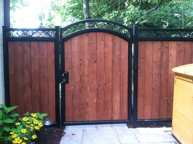 Photo of an iron and wood fence and gate designed and installed by First Fence Company