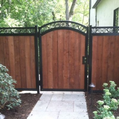 Photo of an iron and wood fence designed and installed by First Fence Company