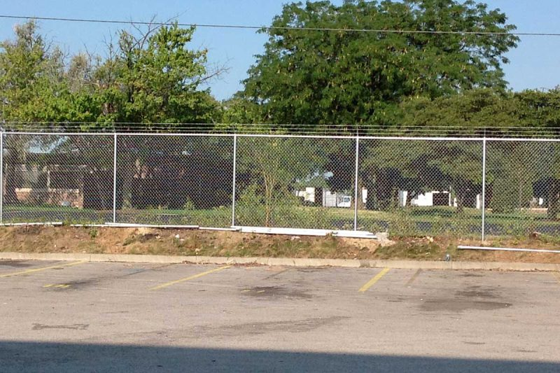 Photo of a custom commercial barbed wire fence installed by First Fence