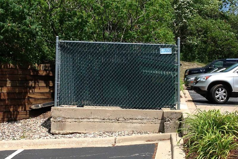 Photo of custom commercial garbage enclosure installed by First Fence