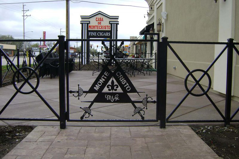 Photo of a custom iron laser cut logo iron fence system - First Fence