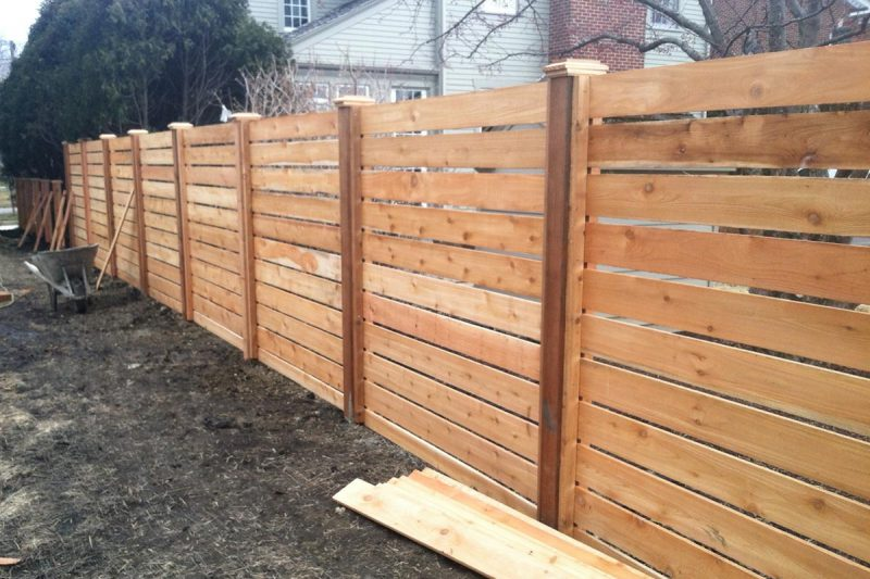 Photo of a custom horizontal pre-stained fence being installed by First Fence