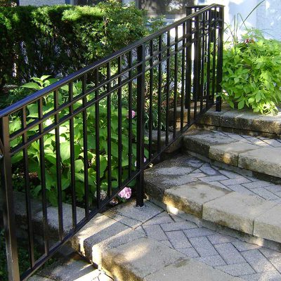 Photo of an iron railing down paver stairs - First Fence