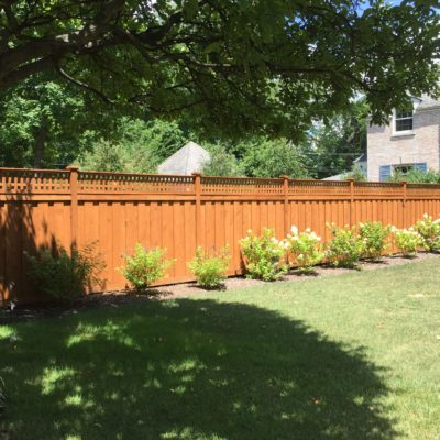 Photo of a custom pre-stained layered traditional wood fence installed by First Fence Company