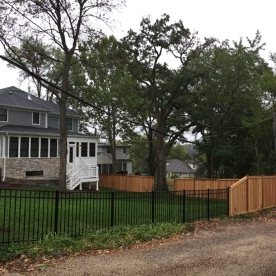 Photo of a wood fence connecting to an aluminum fence designed and installed by First Fence Company