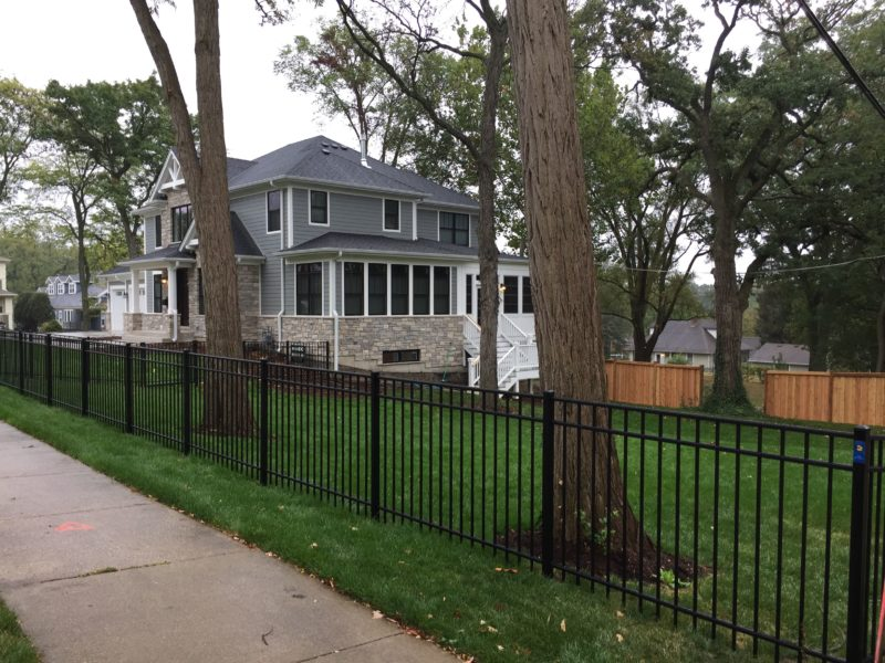 Photo of an aluminum fence connecting to a wood fence designed and installed by First Fence Company